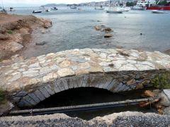 Μικρό Τεχνικό άλλων εποχών. Από την εκβολή της λίμνης στην θάλασσα, στην Σκιάθο. Το παλιό καλντερίμι έχει χαλάσει από την θάλασσα και τις συνεχείς εργασίες στο καρνάγιο.